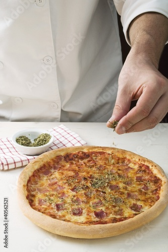 Sprinkling American-style ham pizza with oregano