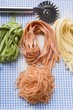 Various types of home-made pasta with pastry wheel