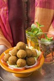 Woman holding tray of falafel (chick-pea balls) and tea