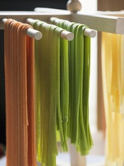 Home-made ribbon pasta hanging up to dry