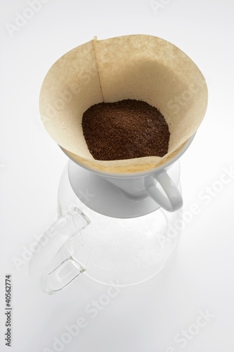 Ground coffee in filter on glass coffee pot
