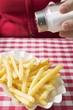Hand sprinkling salt on chips