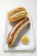 Sausage with mustard and baguette roll on paper plate
