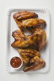 Grilled chicken wings with ketchup on paper plate