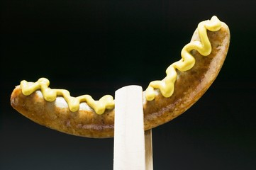 Sausage with mustard in wooden tongs
