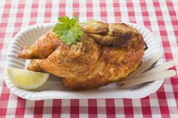 Half a roast chicken in paper dish
