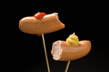 Two half frankfurters with mustard and ketchup