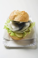 Herring, onions & gherkins in bread roll on paper plate