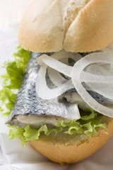 Bread roll filled with herring and onions on paper napkin