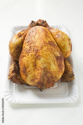 Whole roast chicken on paper plate