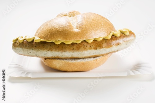 Sausage and mustard in bread roll on paper plate
