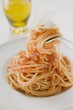 Spaghetti with tomato sauce and Parmesan on fork and plate