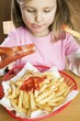 Girl eating chips with ketchup