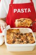 Woman taking portion of lasagne out of baking dish