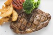 Grilled beef steak with vegetables and potato wedges