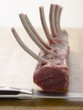 Rack of lamb on chopping board with knife