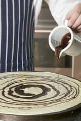 Pouring chocolate onto crêpe