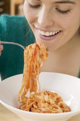Woman eating ribbon pasta with tomato sauce