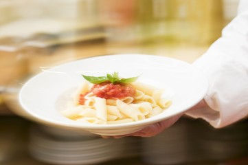 Chef serving penne with tomato sauce