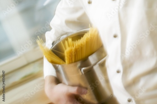 Chef hurrying through kitchen with spaghetti in pan
