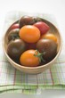 Different types of tomatoes in wooden dish