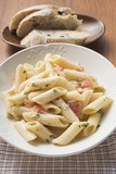 Penne with salmon and cream sauce, slices of bread behind
