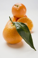 Several clementines, whole and halved, with leaf