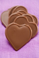 Chocolate hearts on purple background