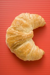 Croissant on red background (overhead view)