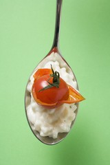 A spoonful of risotto with cherry tomato (overhead view)