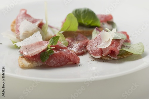 Beef carpaccio with Parmesan shavings on crostini