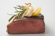 Beef steak, showing cut edge, with garlic, rosemary, lemon