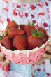 Child's hands holding basket of fresh strawberries