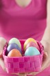 Woman holding basket of coloured Easter eggs