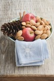 Red apples, almonds and cone in bowl on wooden table