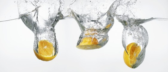 Oranges falling into water