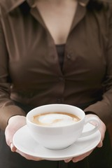 Woman holding large cup of cappuccino