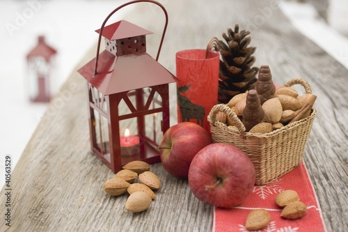 Christmas decoration with apples, nuts & lantern on table