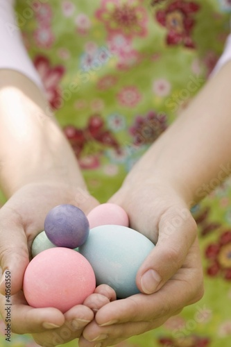 Hands holding coloured eggs