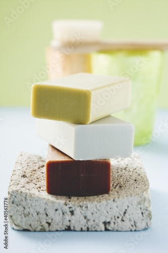 Three bars of soap on pumice stone, windlights, brush