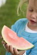 Small girl holding a slice of watermelon with a bite taken