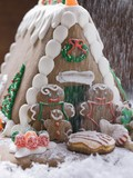 Sprinkling Christmas gingerbread house with sugar