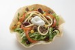 Tortilla shell with mince and bean filling and sour cream