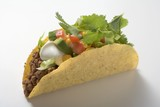 Taco with mince, avocado, sour cream and coriander leaves