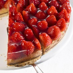 Strawberry flan, partly sliced, with piece on server