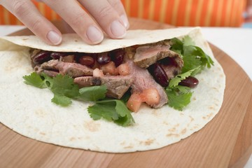 Hand folding tortilla over beef filling