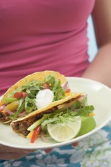 Woman holding plate with two tacos