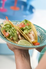 Woman holding plate of two chicken tacos