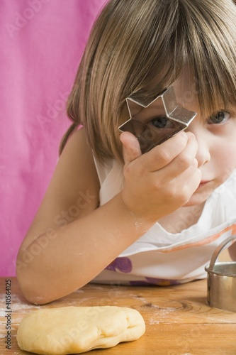 Child peeping through a biscuit cutter