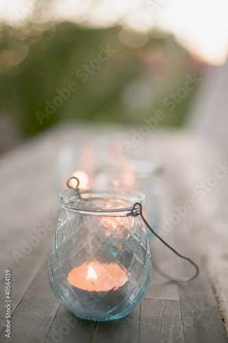 Windlight on wooden table in garden